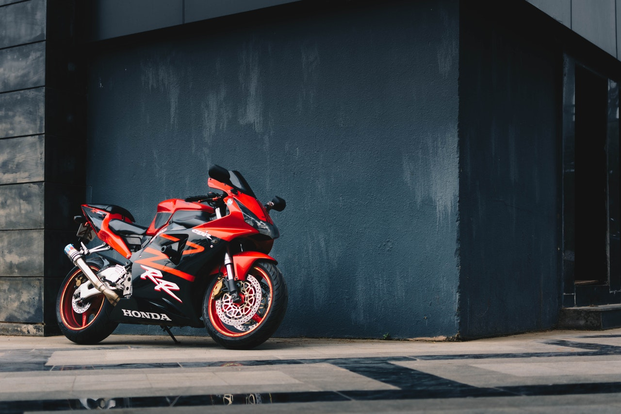 photo of red and black honda sport bike parked next to black 2317519